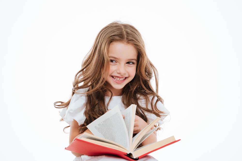 いたずらっぽく笑いながら、本で調べ物をする外国人の少女