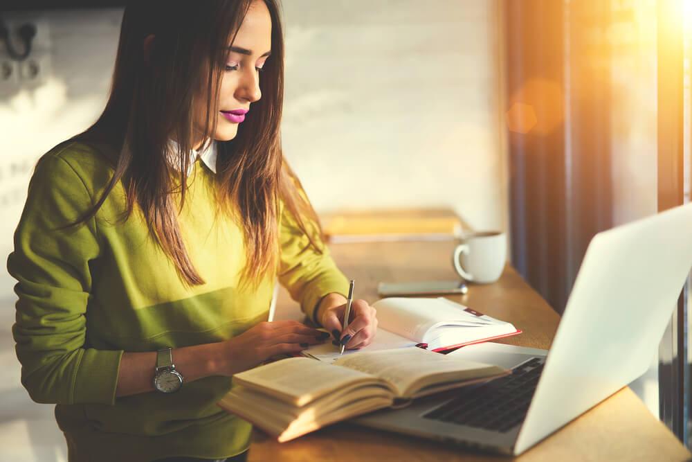 窓辺でコーヒーを飲みながら、勉強をしている外国人女性