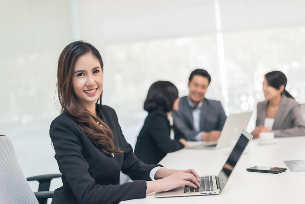 笑顔でPCを操作する総務部の女性