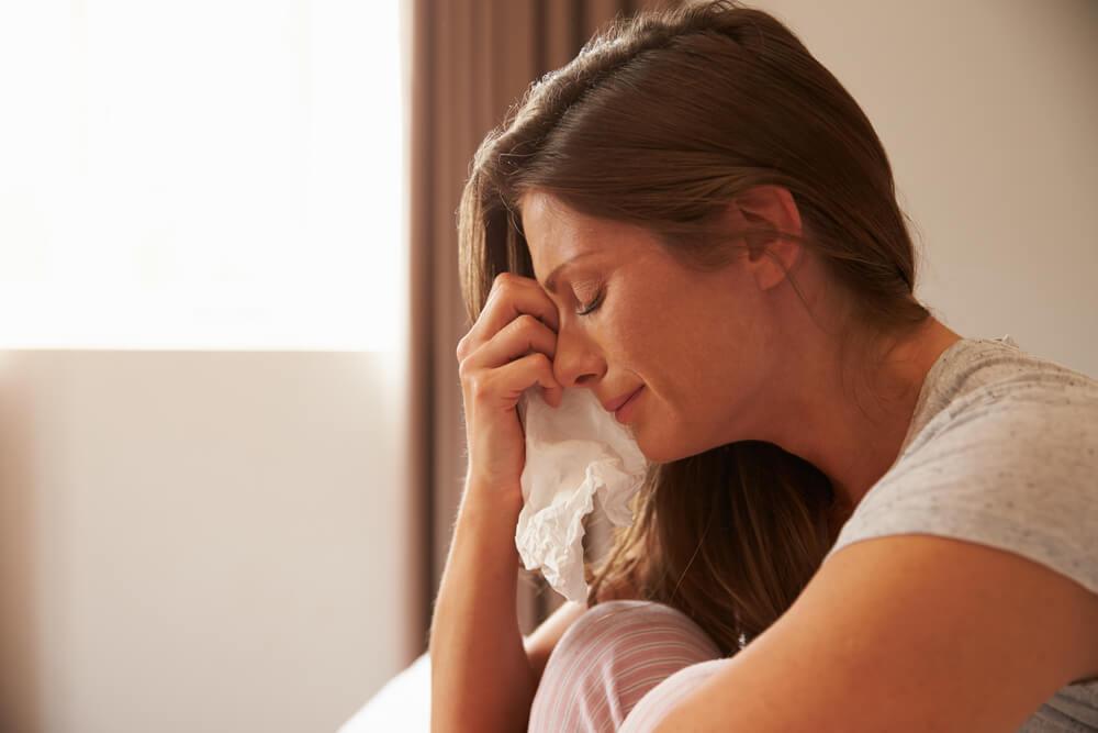 ベッドで泣き崩れる外国人女性