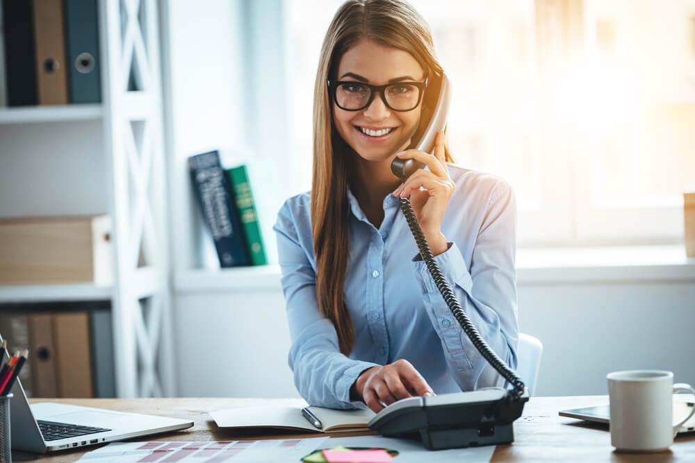 オフィスで電話を受けながら、こちらに笑顔を送る外国人女性