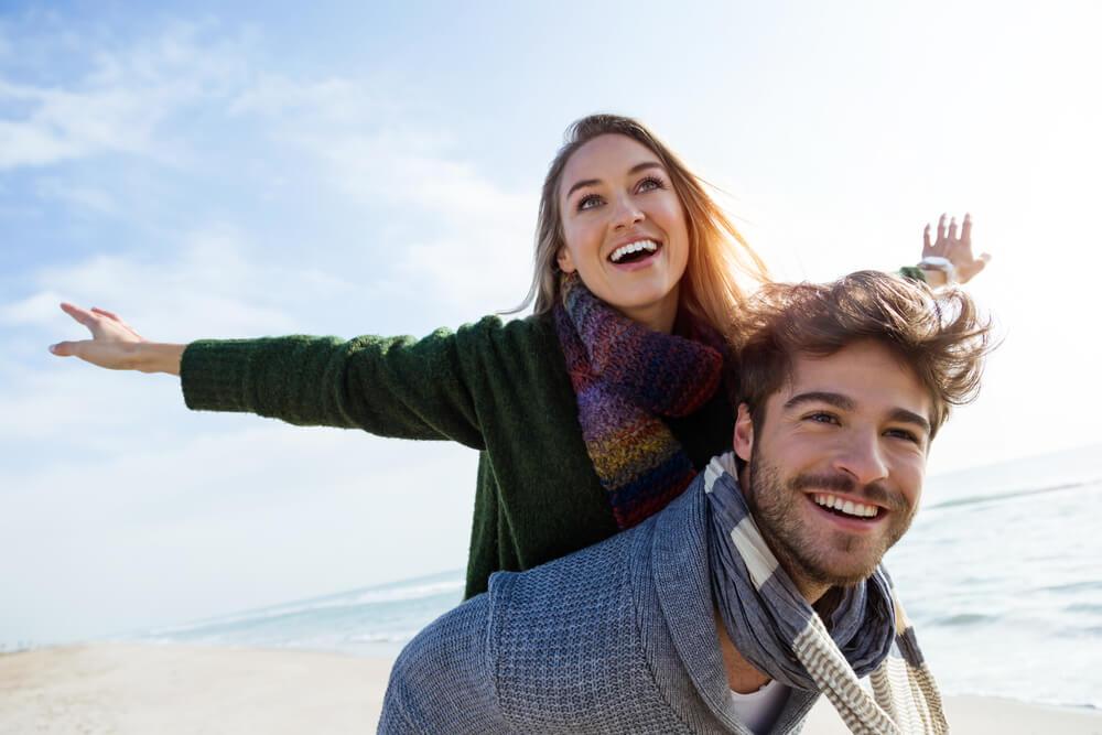 海辺で女性を背中に背負う外国人男性