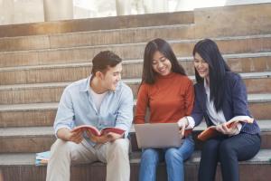 外国人留学生が増えれば、国際結婚の減少はストップし、増加に転じる。階段に座って談笑する留学生たち