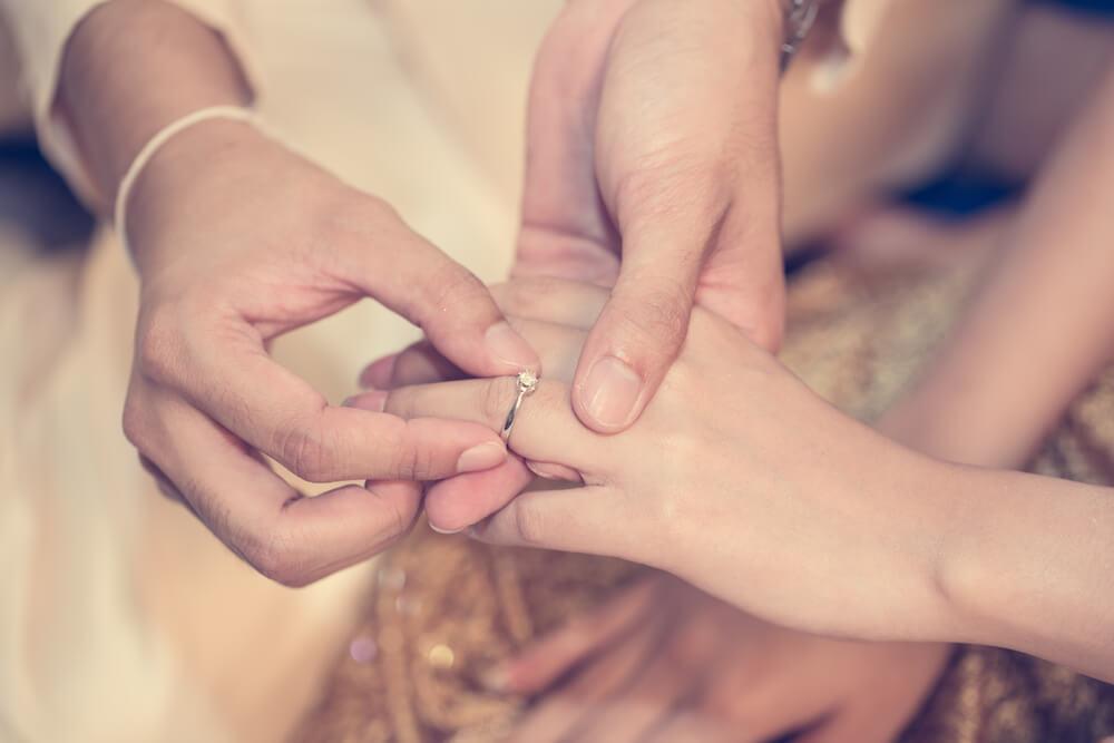 男性が女性の薬指に結婚指輪をはめている