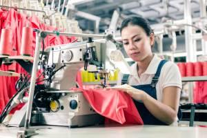 国際結婚した外国人女性。生活に必要な世帯年収を上げるために、工場でミシンを扱うアジア人女性