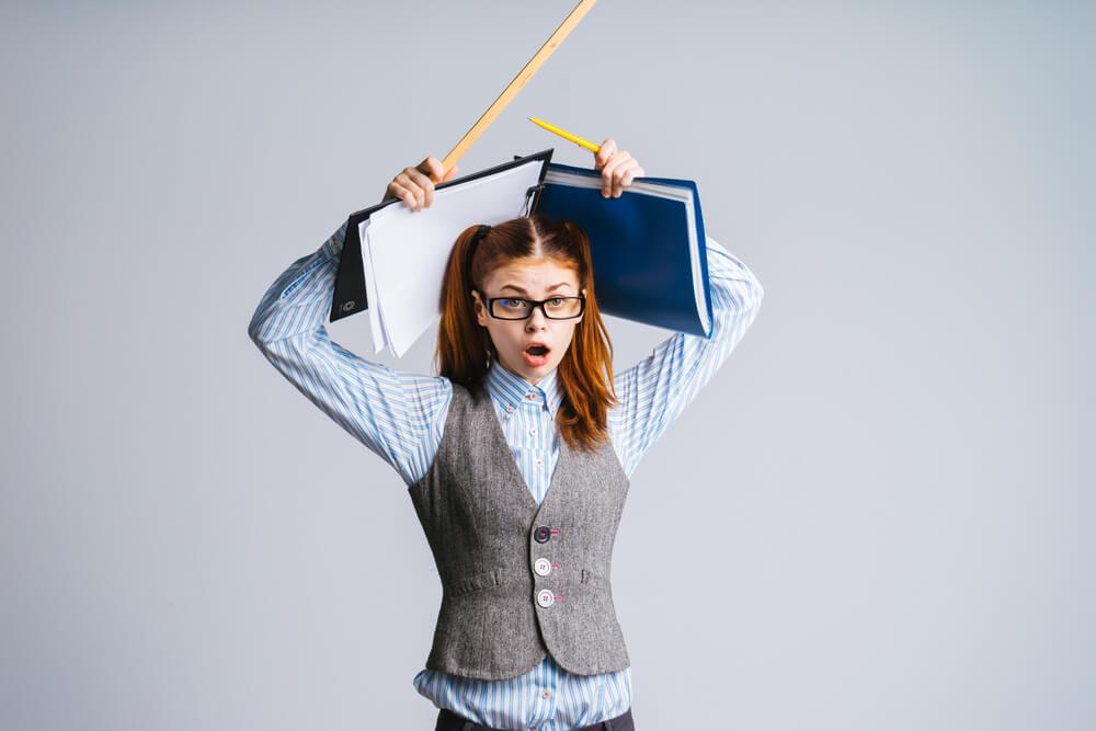 持っている道具を頭の上にかざして、どうしていいかわからない外国人女性