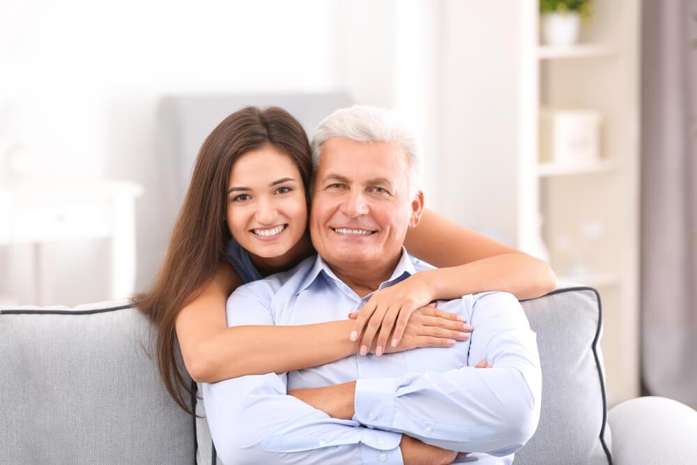 親子ほど年が離れた国際結婚カップル。若い女性が年齢がかなり高い男性に抱きついている