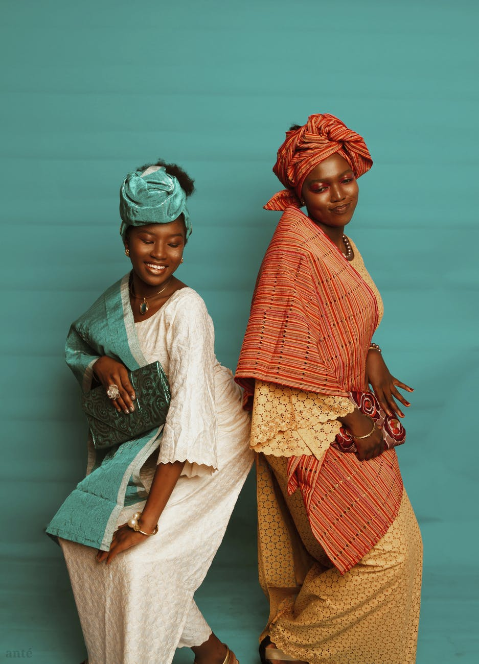 black women in traditional dresses and headdress near blue wall