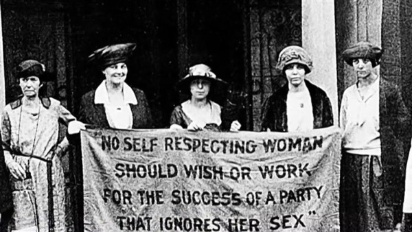 Women standing with a banner right to vote