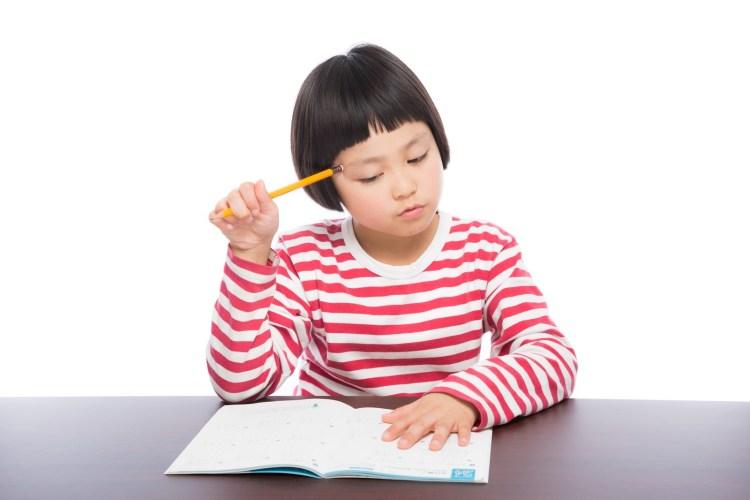 鉛筆をもって宿題をしようとしている小学生