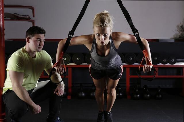 金髪女性が運動している姿を見つめる男性