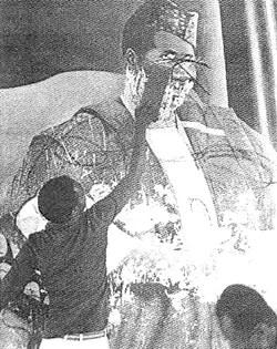 Le 3 avril 1984, le peuple de Guinée est délivré de la tyrannie qui a duré 26 ans. Un gosse efface un portrait du sanguinaire Sékou Touré. Source: campboiro.org