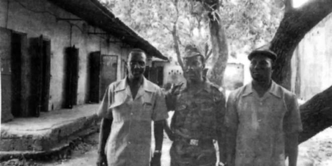 Bâtiment n°6. Avec, au fond, le réduit servant de local pour la vidange journalière. Alsény R. Gomez à gauche, pose ici en compagnie duLieutenant-Colonel Kaba 41 Camara, au centre, qu'il omet de nommer par deux fois. Le troisième individu n'est pas identifié.