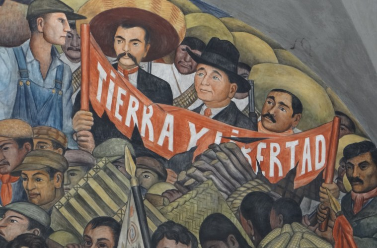 "Part of Diego Rivera's ""History of Mexico"" mural at the National Palace in Mexico City. The cropped portion features the images of Emiliano Zapata (left with sombrero), Felipe Carrillo Puerto (center), and José Guadalupe Rodríquez (right with sombrero) behind banner featuring the Zapatista slogan, Tierra y Libertad (Land and Liberty). 18 May 2012. Source: Self-photographed. Author: Cbl62. Public Domain."