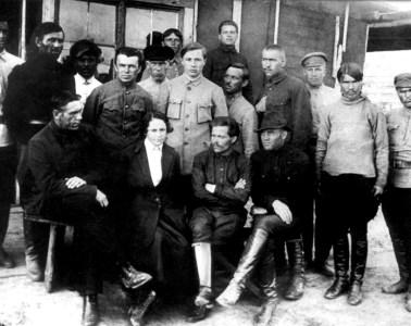 Nestor Makhno med sin hustu omgivet af af medaktivister. 1920, ukendt fotograf. Public domain.