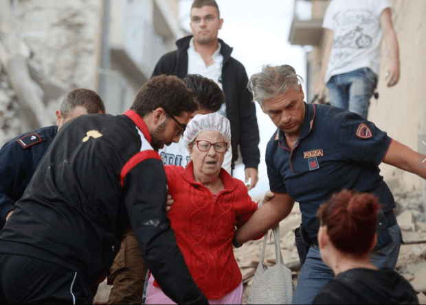 Italian Earthquake9: Rescuers help a woman among damaged buildings after a strong heartquake hit Amatrice on August 24, 2016. Central Italy was struck by a powerful