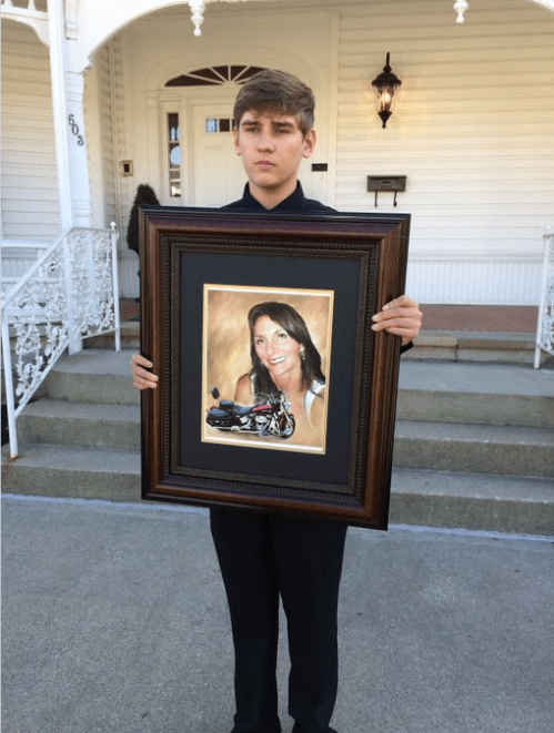 Wendy Sabatini's son Eaton with his mom's photo.png