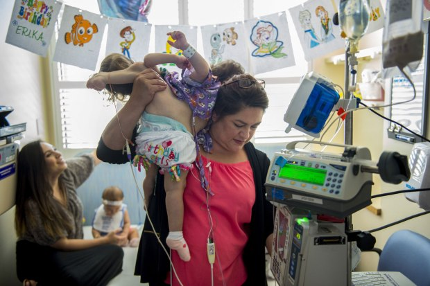 Aida Sandoval rests twins Eva and Erika on her shoulders during a hospital visit.jpg