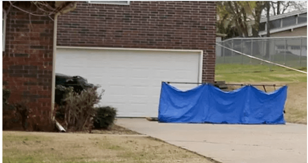 Two of the teens died in the kitchen, while a third (pictured, with his leg emerging from the tarp) ran to the driveway and collapsed
