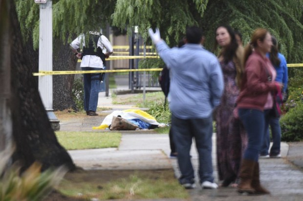 Evacuated office workers stand by, with a deceased shooting victim down on the sidewalk in Fresno, California