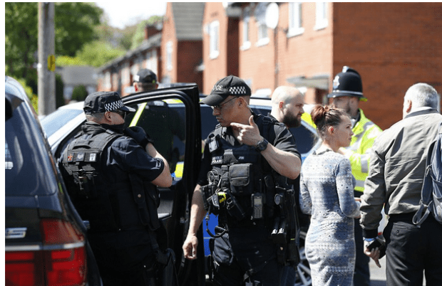 Security officers swarm the street in the south of Manchester today to search a house where the Abedi's are believed to have lived.png