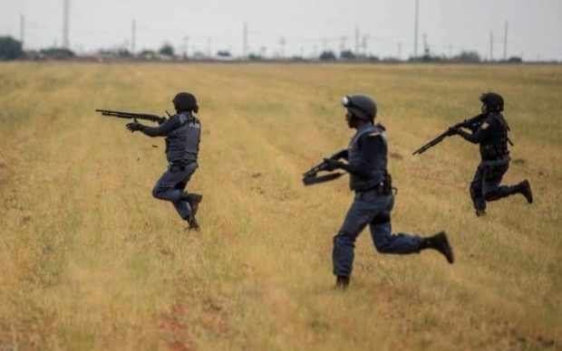 South African riot police officers run to disperse protesters in Coligny1
