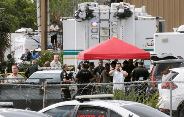 Deputies and other law enforcement officials at the scene in Orlando, Monday.png