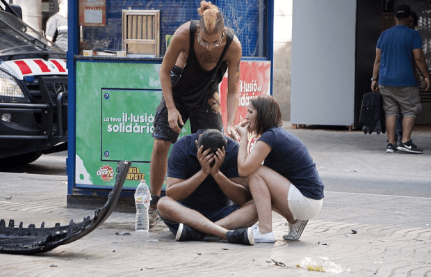 A man sits on the pavement with his head in his hands after the Barcelona attack,.png