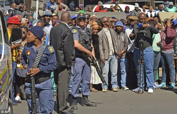 Armed police stand guard outside the magistrates court in Estcourt, South Africa,.jpg