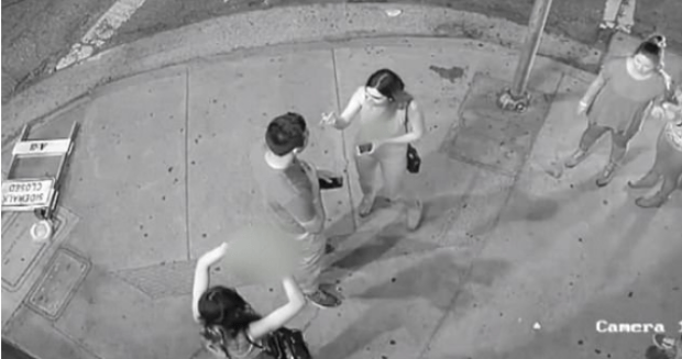 Outside the nightclub, the woman (left) is seen making a sexual gesture to a friend - poking a finger through a circle made with her hand.png