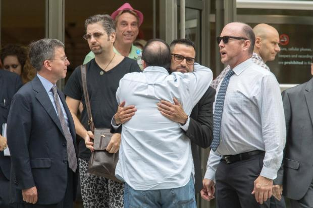 Jeffrey Hurant, center, is hugged by a reporters as he leaves Federal court