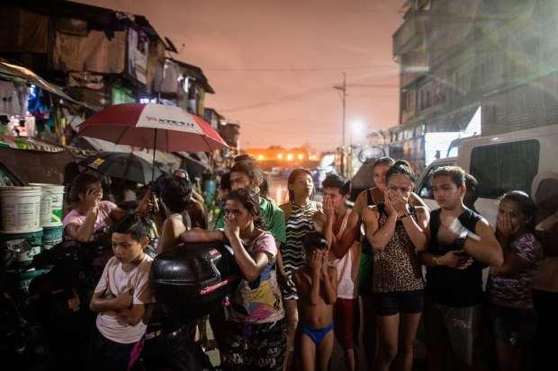 Locals gawk in shock near a scene where three alleged drug dealers were killed after a raid in Manila