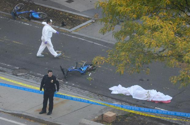 A police officer and investigator guard the body of a victim [under white tarp] at the scene of the Tuesday terror attack.