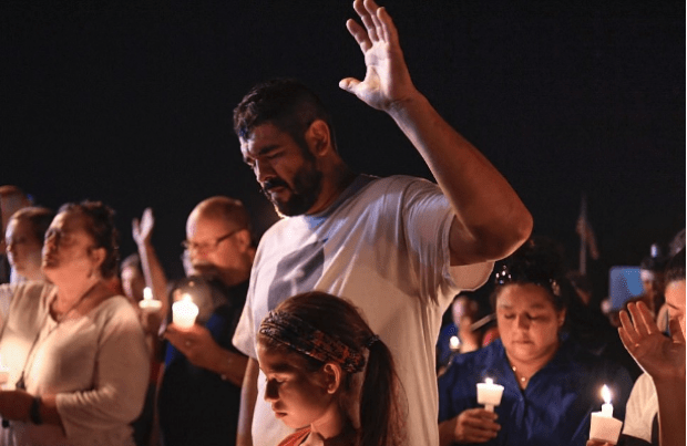 During aVigil held after dozens are killed in a church shooting in Texas, a man raises his right hand and bows his head.png