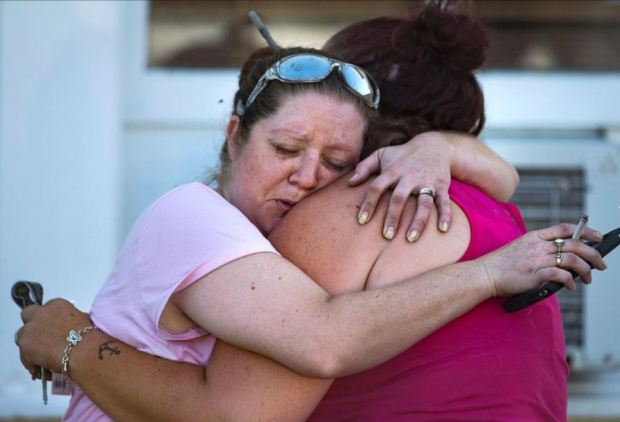 Members of the community hug and comfort each other