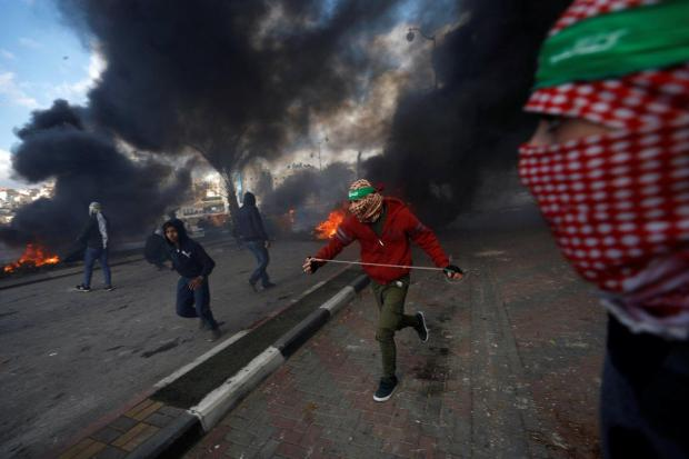 Palestinian run protesters during clashes with Israeli troops in Gaza strip.jpg