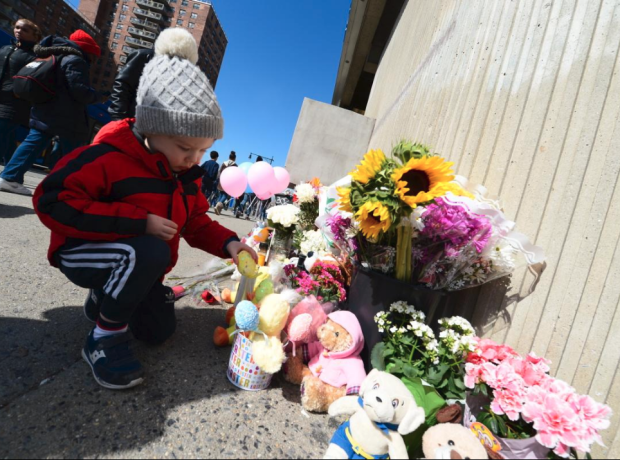 A child places flowers at the memorial site for the young victims.png