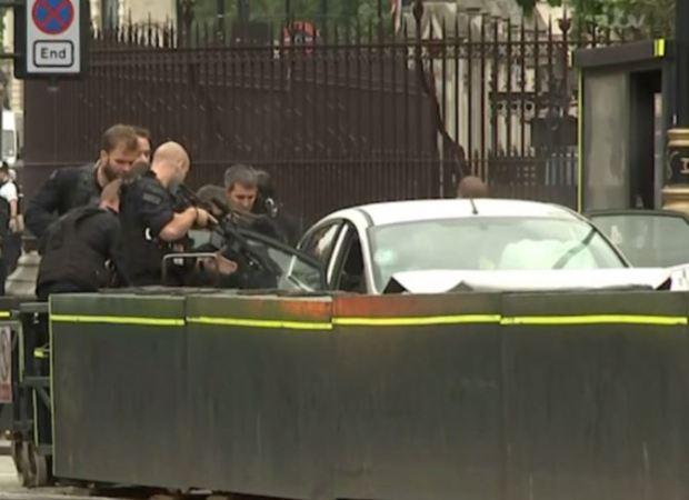 Armed officers swamp a crumpled silver car.JPG