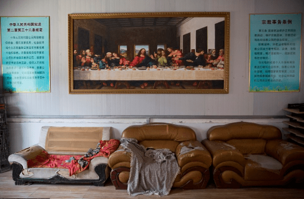 Ppainting of the Last Supper is seen next to posters quoting China's constitution on religious freedom in a house church shut down by Chinese authorities in Nanyang3.png