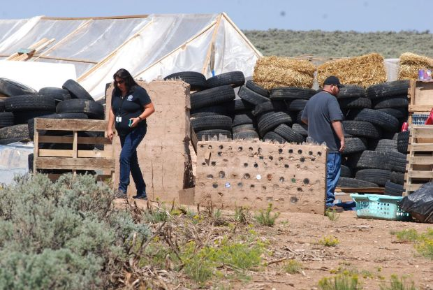 Taos County, N.M., Planning Dept officials survey disheveled compound in Amalia on Tuesday