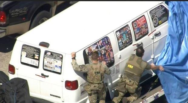 Law enforcement wrap Cesar Altier Sayoc's white van with a tarp.JPG