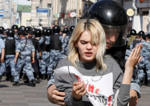 Female protester is dragged away by a security officer in Moscow 1.JPG