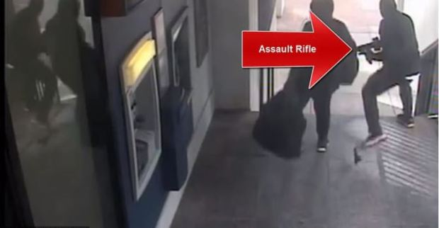 The robbers confront the guards before they grab heavy bags loaded up with cash.JPG
