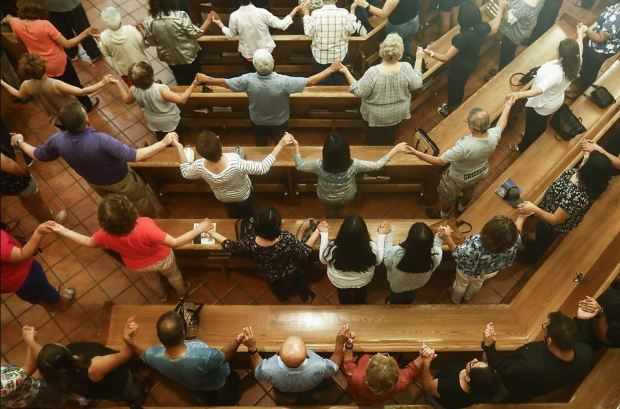 Worshippers holdd hands during a vigil for victims at St Pius X Church 1.JPG