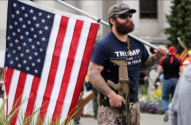Justin Bailey, holds an assault rifle and a flag as he protests in Tacoma, Wash 1