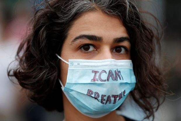 Protester wearing a face mask with the I can't breathe written across her mouth
