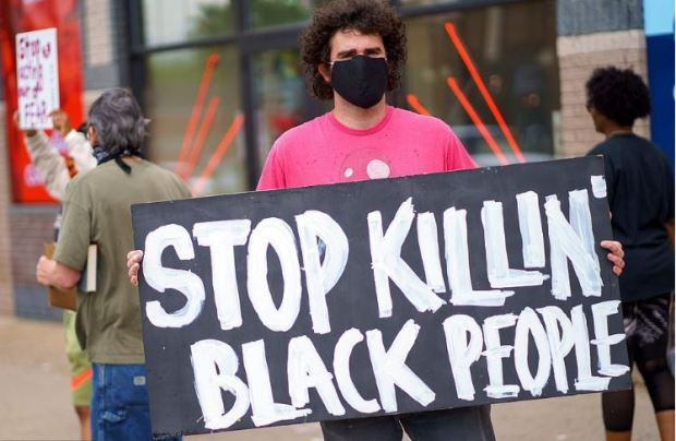 Protester with 'Stop Killing Black People' placard protesting near spot where a Minneapolis cop killed George Floyd 1