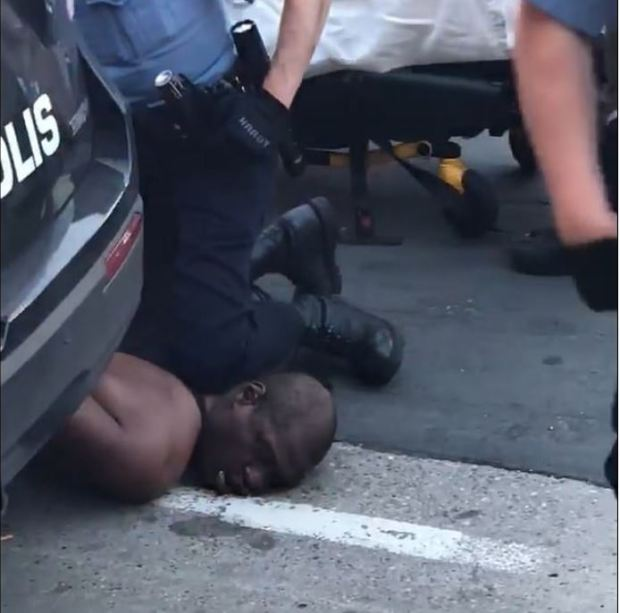 White Minneapolis police officer pins  a black man to the ground with his knees 2