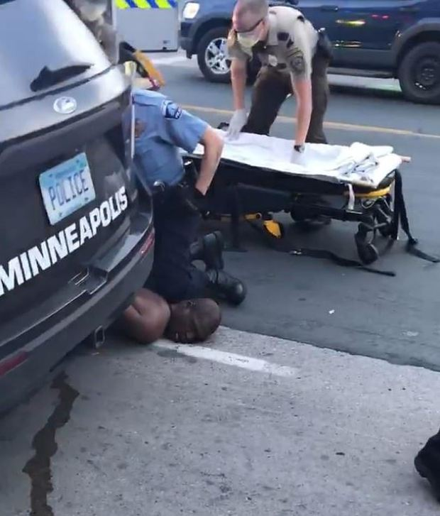 White Minneapolis police officer pins  a black man to the ground with his knees 5