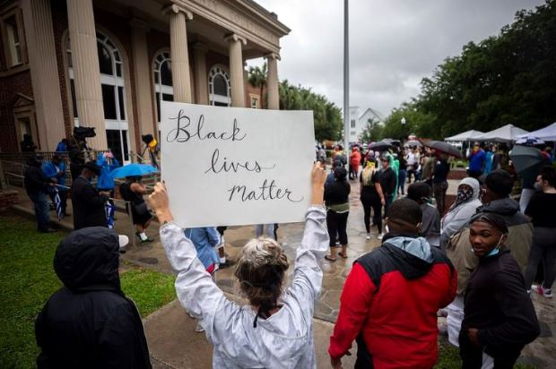 Protesters hold up Black Lives Matter placard